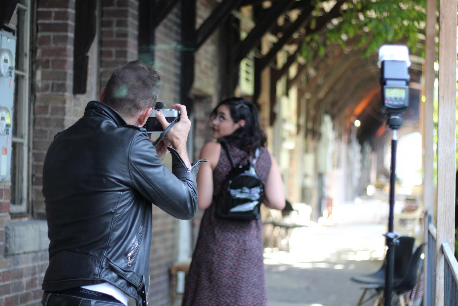 Tyson Call directs Maria Torres during a photography demonstration in SLUG's backyard.